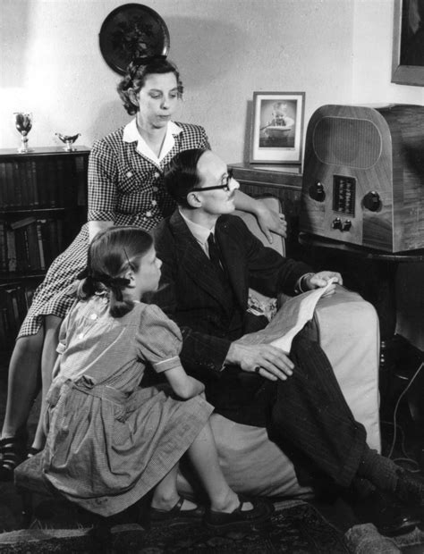 A family grouped around a wireless set listening to BBC ...