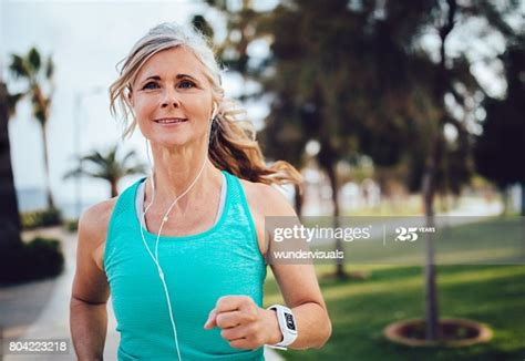 Active Mature Woman With Headphones And Smartwatch Running ...