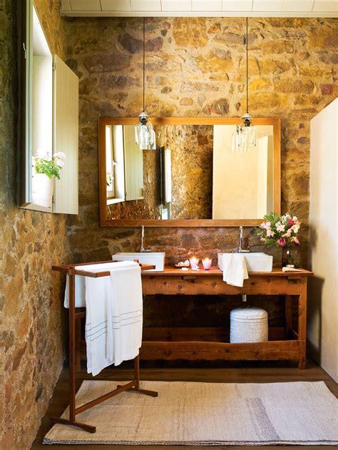 Baño de pared de piedra y obra con mueble de madera ...