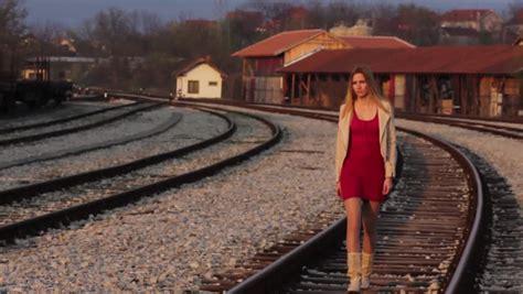 Beautiful young girl walking on the railway track ...