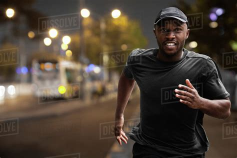 Black man running on city street at night   Stock Photo ...