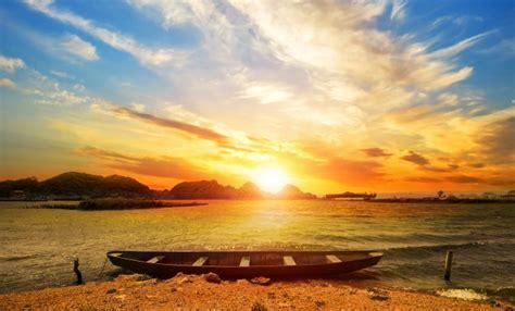 Bonito paisaje de playa al atardecer con una barca ...
