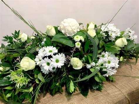 centro de flores naturales, con tonos suaves, flores funebres