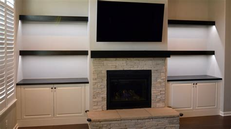 Custom built in cabinets, floating shelves and fireplace ...