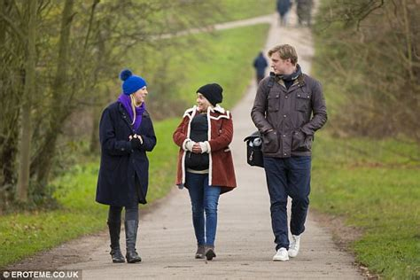 Emilia Clarke cradles godson around Hampstead Heath ...