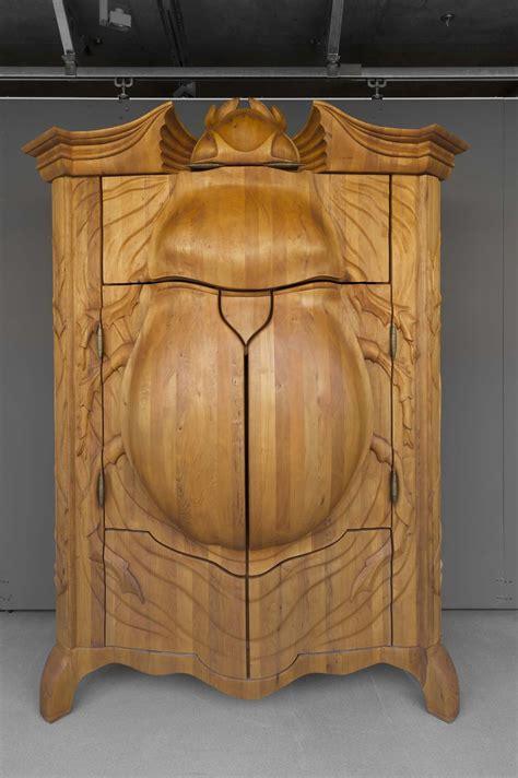 Escultura y mueble en madera con un escarabajo tallado a ...