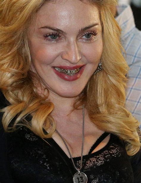 Grill girl... Madonna flashes a blinging, blinding smile ...