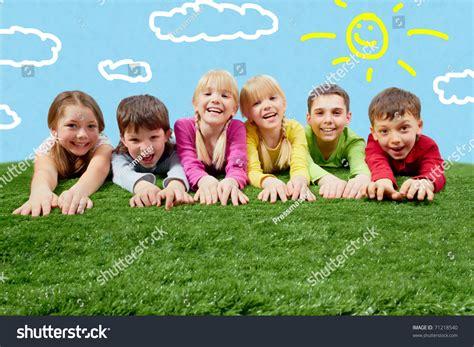 Group Of Happy Children Lying On A Grass And Stretching ...