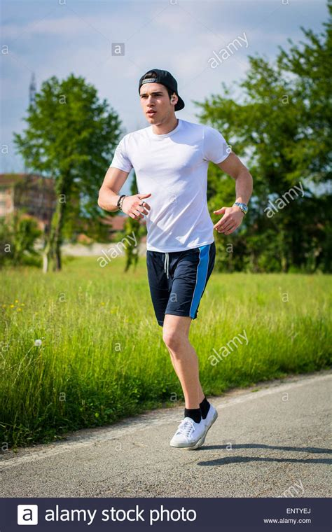 Handsome young man running and jogging on road in the ...