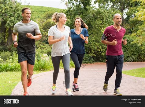 Healthy Group of People Jogging on Track in Park Happy ...