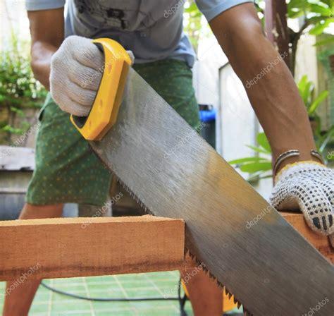 joven aserrar madera en uso en el hogar para trabajo de ...
