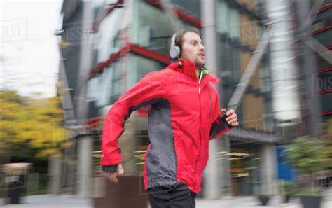 Man running with headphones past urban building   Stock ...