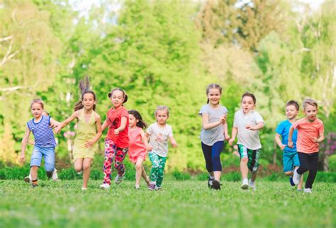 Many different kids, boys and girls running in the park on ...