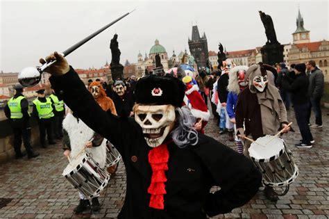 Personas con máscaras desfilan por el puente medieval ...