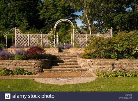 Plantas y arbustos soleada pared de piedra, pasos ...