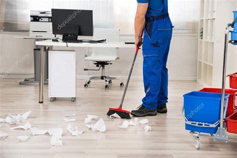 Portero barriendo el piso con la escoba en la oficina ...