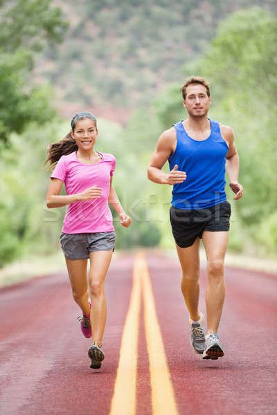 Running people   two smiling runners jogging stock photo ...