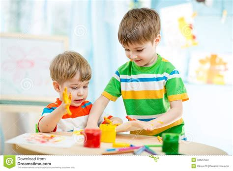 Smiling Kids Play And Paint At Home Or Stock Photo   Image ...
