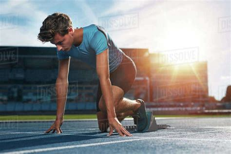Young male athlete at starting block on running track ...